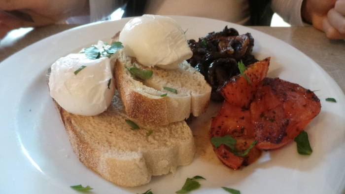 Poached eggs on toast with mushroom and tomato